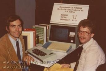 Two men smiling and sitting at a desk with a computer and books.
