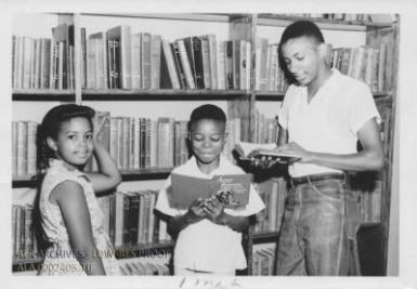 A group of children smiling and standing in front of books stacks.
