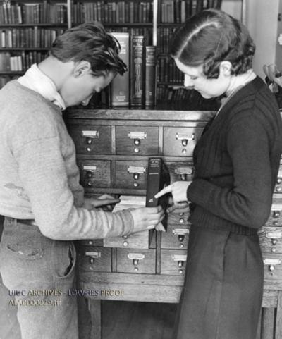 People opening the drawer of a card catalog and pointing to the call number of the spine of a book.