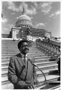 A man talking into a microphone in front of the U.S. Capitol, which has construction scaffolds in front of it.