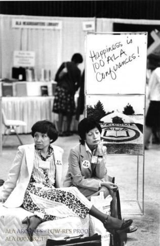 "Two librarians sitting on the floor of a conference hall under a sign that says ""Happines is 100 ALA Conferences."""