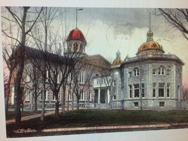 An external picture of a building that has a golden dome over a rectangular part and a golden dome over a circular part. A line of trees stands in front of the building. There is a faint postal stamp. A banner at the botton reads