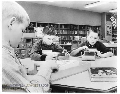 Children sitting at a table, looking through card catalog drawers.