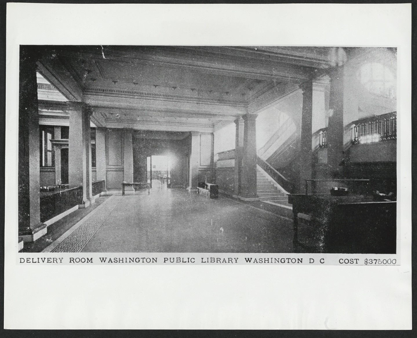 The interior of a large room. Plentiful sunshie pours through windows into the room. Work desks are featured along the walls. A staircase leads upward. An original caption at the bootom of the picture reads: Delivery room Washignton Public Library, Washington DC Cost $375000""
