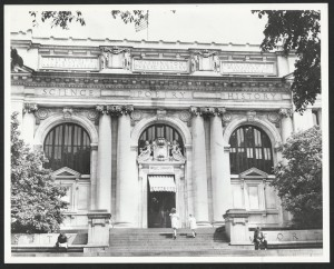 """A picture of the facade of Central Library in Washingto DC. The ornate building has three arched windows, an American flag on top, a door with a canvas over the top, sculpted figures atop the doorway and near the roof who are holidng books. The building also has these etchings in large letters: Science. Poetry. History. This building a gift of Andrew Carnegie. Washington Public Library. Dedicated to the diffusion of knoweldge."""" People walk and read on the steps leading to the door."""