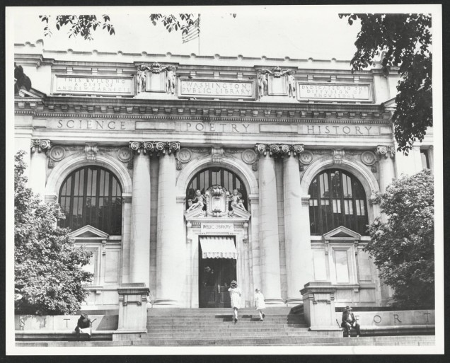 "A picture of the facade of Central Library in Washingto DC. The ornate building has three arched windows, an American flag on top, a door with a canvas over the top, sculpted figures atop the doorway and near the roof who are holidng books. The building also has these etchings in large letters: Science. Poetry. History. This building a gift of Andrew Carnegie. Washington Public Library. Dedicated to the diffusion of knoweldge."" People walk and read on the steps leading to the door."