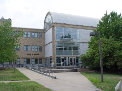 An external view of the University of Missouri School of Medicine, which contains a library. The brown building has lots of windows and a rotunda.
