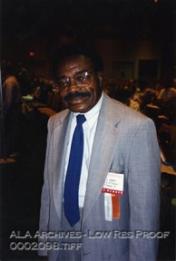 An African-American man in a blue suit, tie, name tag. Conference attendees are in the background.