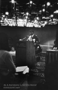 In a darkened room, an African-American man speaks to an audience.