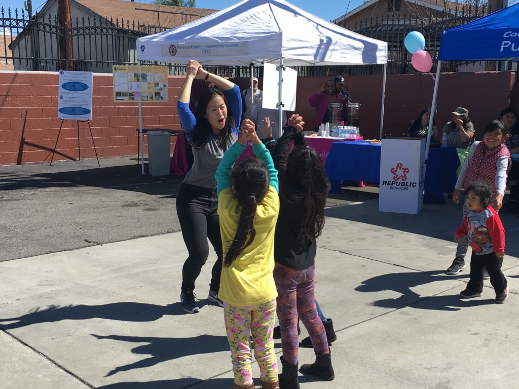 An adult and several children are dancing in front of display tables.