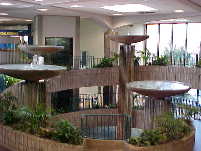 Fountains, shaped like bowls on columns, stand in the center of a building surrounded by plants and large windows