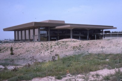 An image of Huntington Beach Public Library. Its beige facade blends with the surrounding desert.