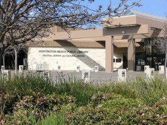 The front of the Huntington Beach Public Library--Central Library and Cultural Center. Biege and brown building with a plaza