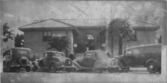 Black-and-white photo of building with gabled roof. Palm trees and older model cars in front.