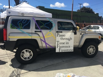 "A silver hummer vehicle with purple, green, blue decorative stripes and a sign reading ""Paseo Through Time Time in Florence-Firestone"""