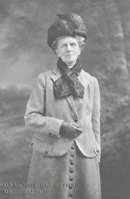 A black-and-white photo of a woman in early 20th century fashion.