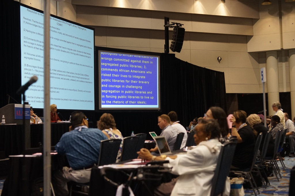 A crowd of people at rows of tables with laptops. Two large screens in fron of the audience. A panelp of people at the front of the room.