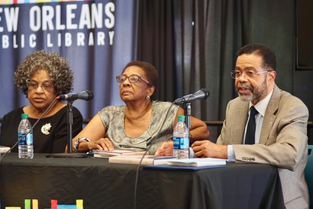 """2 women and 1 man at a black table with microphones. A """"New Orleans Public Library"""" banner in the background."""