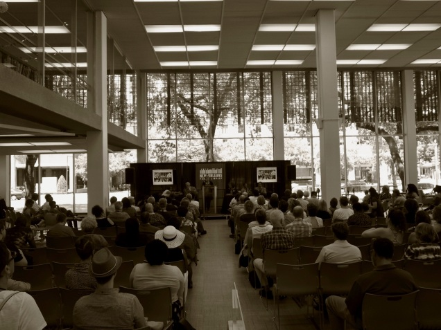 """A black-and-white photo of a crowd of people facing a presenter, banner in background says """"New Orleans Public Library"""" and photos of a protest."""