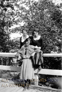 A group of three women in a b & w picture, two of the women are sitting on a bridge rail.
