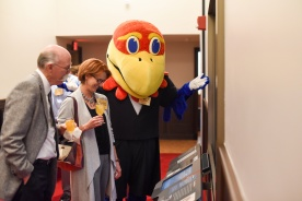 A large orange bird points out items in a display to interested guests carrying drinks.