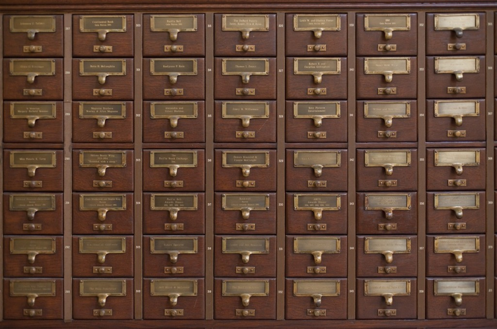 A brown, wooden card catalog with brass handles