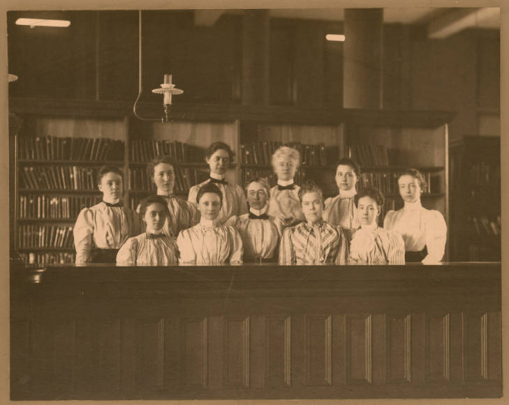 "Description from Omaha Public Library digital archives: ""Eleven women are shown behind a wooden counter. Edith Tobitt, Library Director at the time, is the only identified person. She is in the center of the group, wearing glasses."""