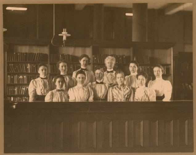 """Description from Omaha Public Library digital archives: """"Eleven women are shown behind a wooden counter. Edith Tobitt, Library Director at the time, is the only identified person. She is in the center of the group, wearing glasses."""""""