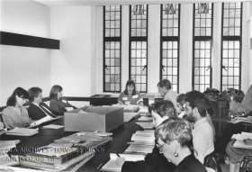 A group of people sitting around a large table, the table has a big box in the center, and piles of old documents and books.