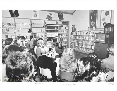 a group of library staff sit in chairs watching a TV set against a backdrop of book stacks